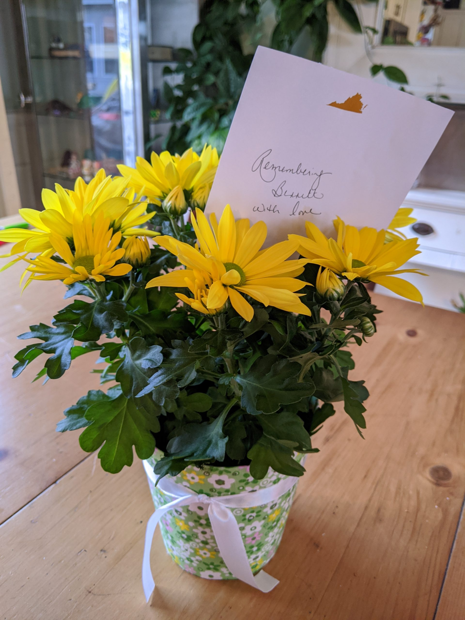 photo of yellow daisies and a note that says remembering Bennett with love