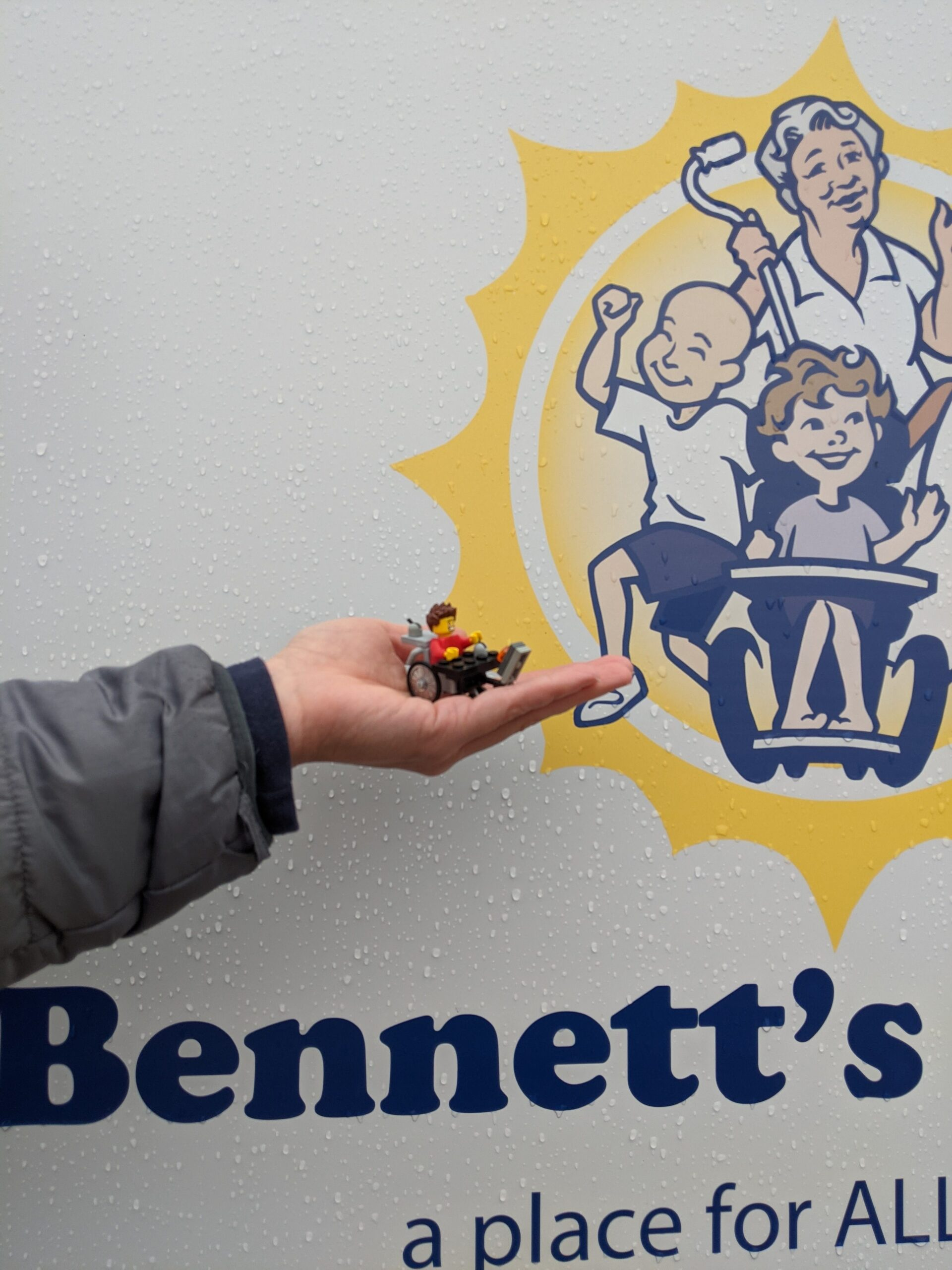 Lego Ben in his wheelchair is being held next to the Future Home of Bennett's Village sign. Lego Ben has brown, wavy hair, a huge smile, and a red shirt.