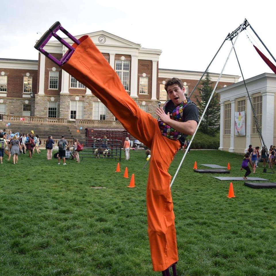 Mike Giovinco is on stilts and kicking his right stilted leg above his head. His pants are orange and he is wearing a dark-colored shirt. In the background is a rig for aerial acrobatics.